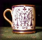 A small cup decorated by Arthur Midgley